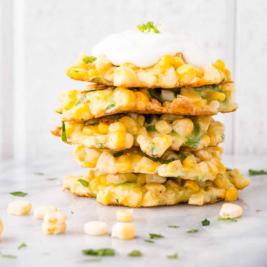 Corn Fritters in a stack with a dollop of sour cream on top.