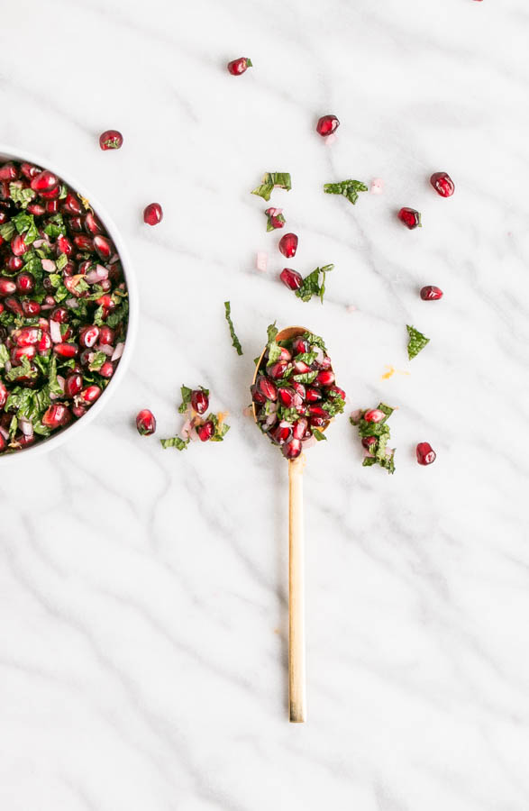 Deep red Pomegranate Mint Relish on a spoon and scattered on a marble countertop.