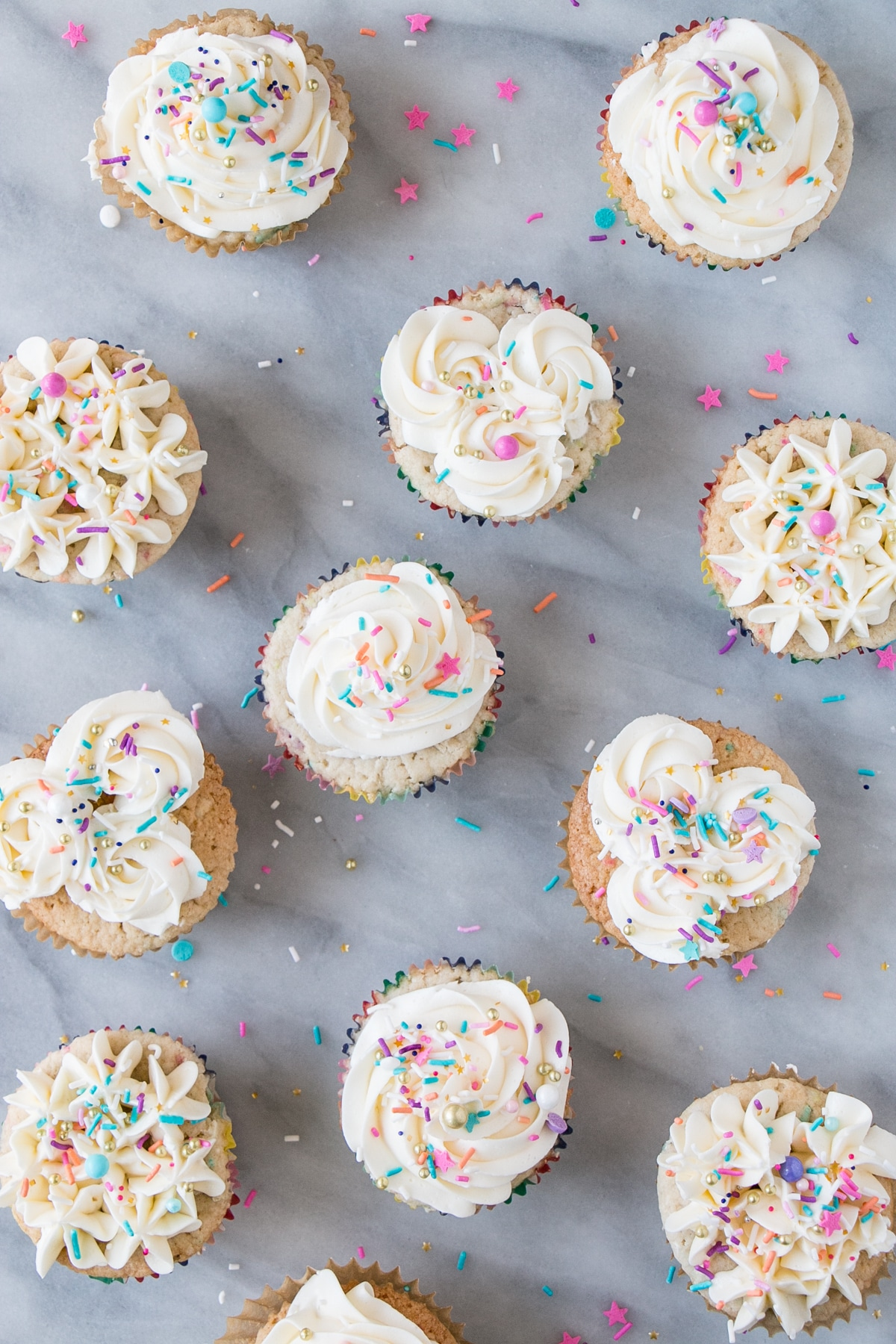 Momofuku Milk Bar Cake turned Birthday Cupcakes. Top down photo with sprinkles.