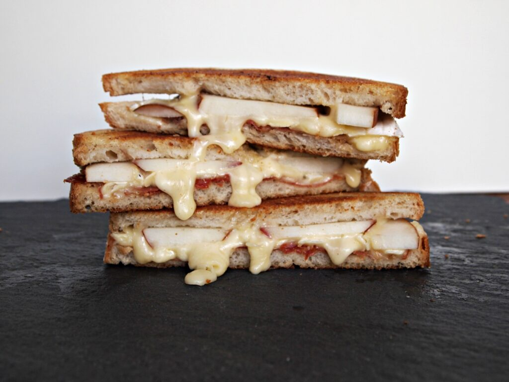 Brie cheese dripping down 3 sandwich halves.