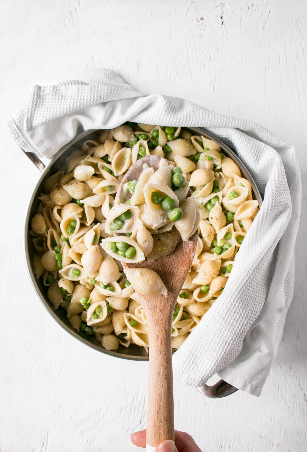 Lemon Pepper Alfredo in a large serving spoon over top of a skillet