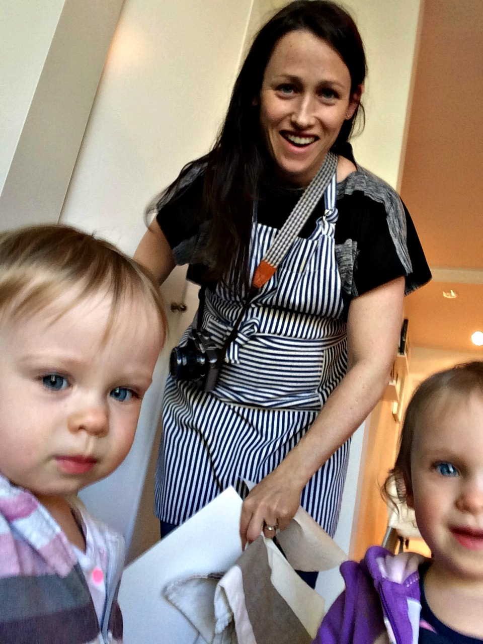 a brunette with an apron one and a camera around her neck with 2 toddlers.