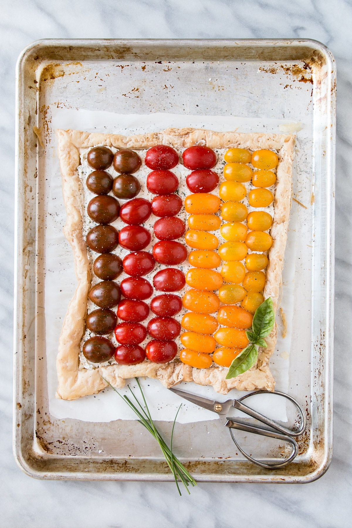 Tomato Tart on parchment paper with herbs.