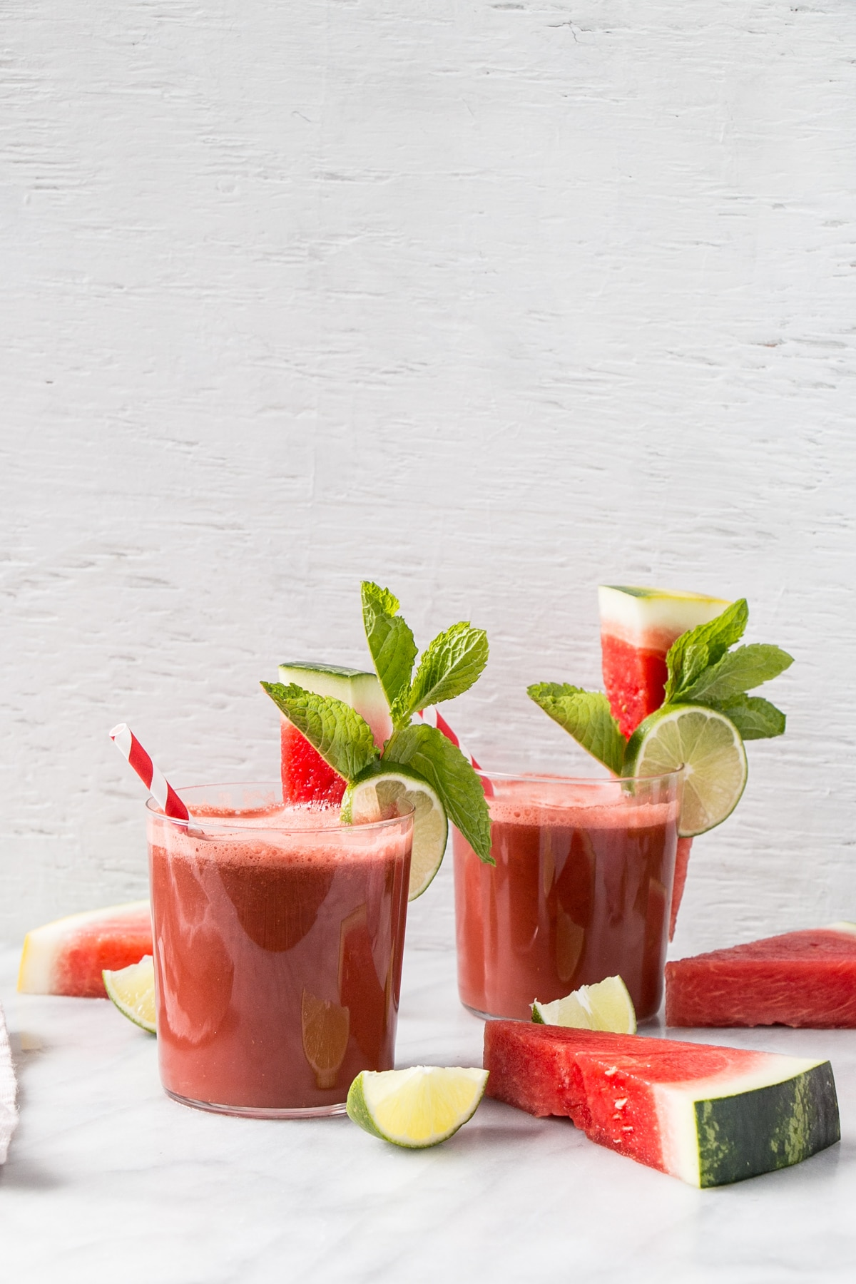 watermelon smoothie with watermelon mint and lime garnishes in glasses