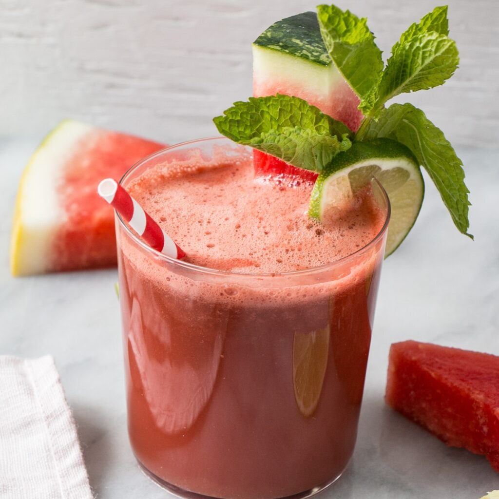 Watermelon Smoothie in a short clear glass with a slice of watermelon, mint leaves, and a lime on the side.