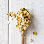 Grilled Corn and Avocado Salad on a wooden spoon with a white background.