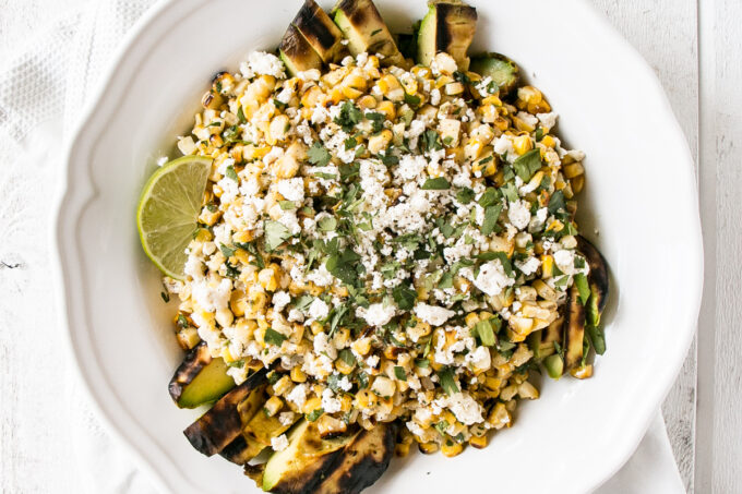 Grilled Corn and Avocado Salad with cilantro and feta cheese in a white serving bowl.
