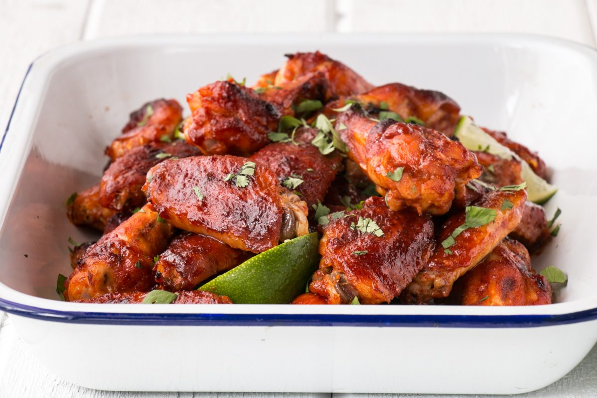 gochujang hot wings in a white serving tray