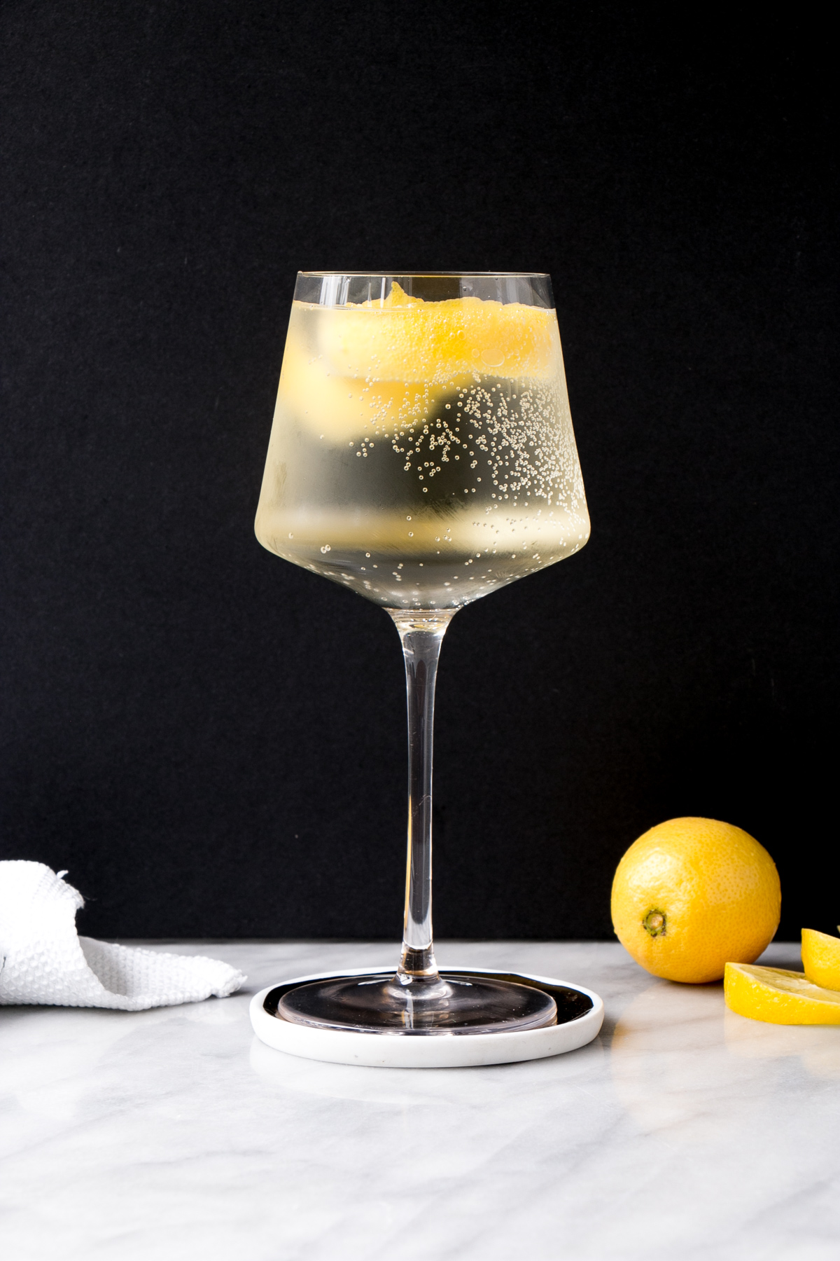 White wine spritzer in a tall wine glass with lemon rind in it.