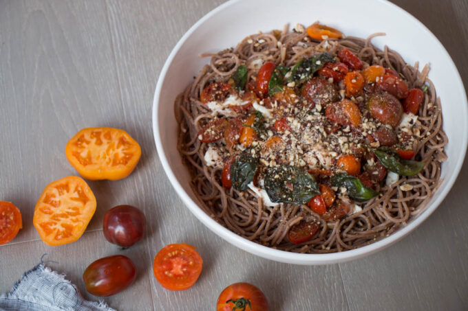 spaghetti with tomatoes and hazelnuts in a bowl with tomatoes beside it.