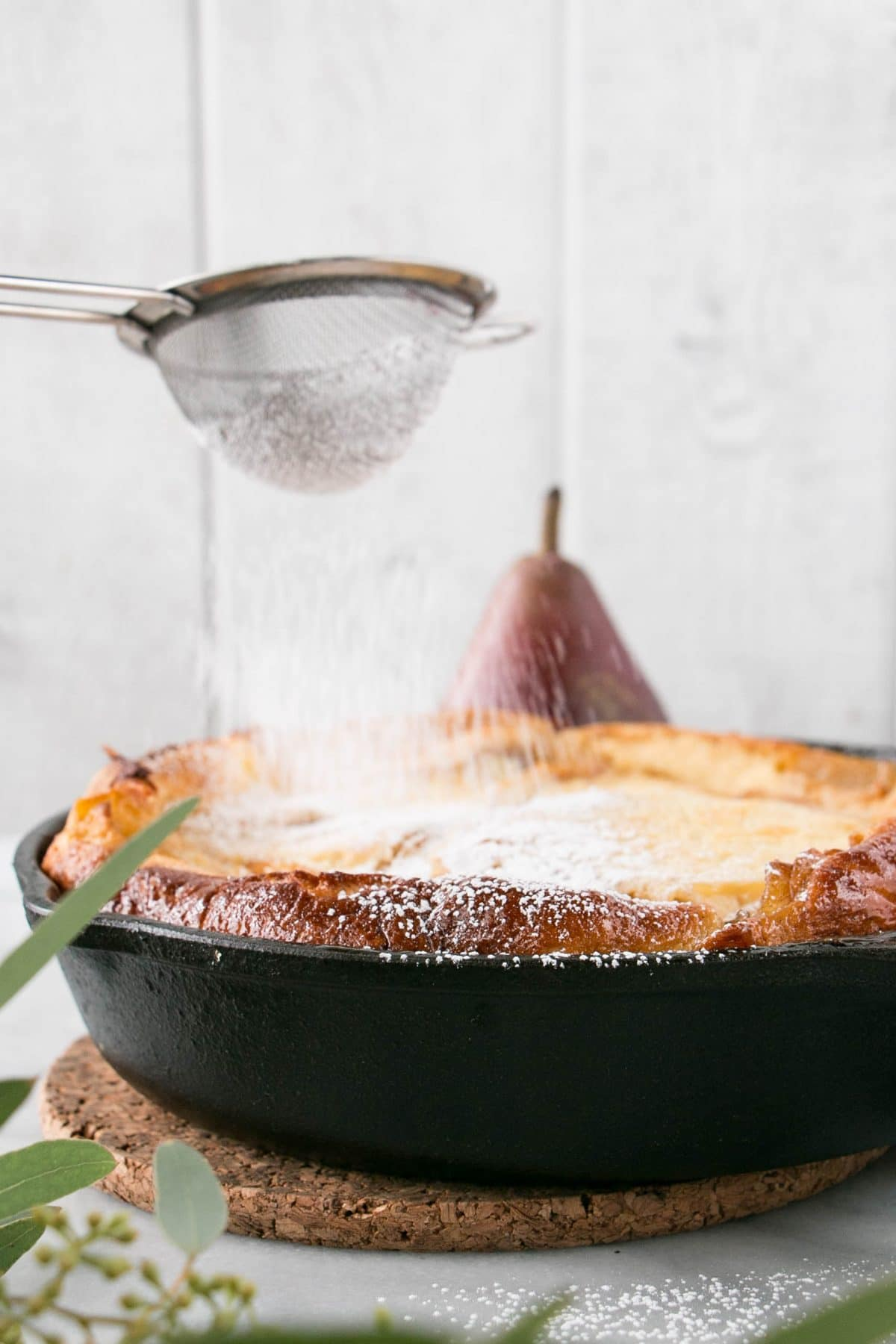 Icing sugar being sifted onto a Baby Dutch Pancake in a cast-iron skillet with a red pear in the background.