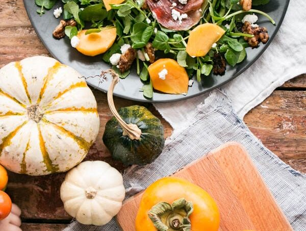 Persimmons and Watercress Salad with Candied Walnuts and Goat's Cheese on a black plate with Fall gourds and persimmons nearby.
