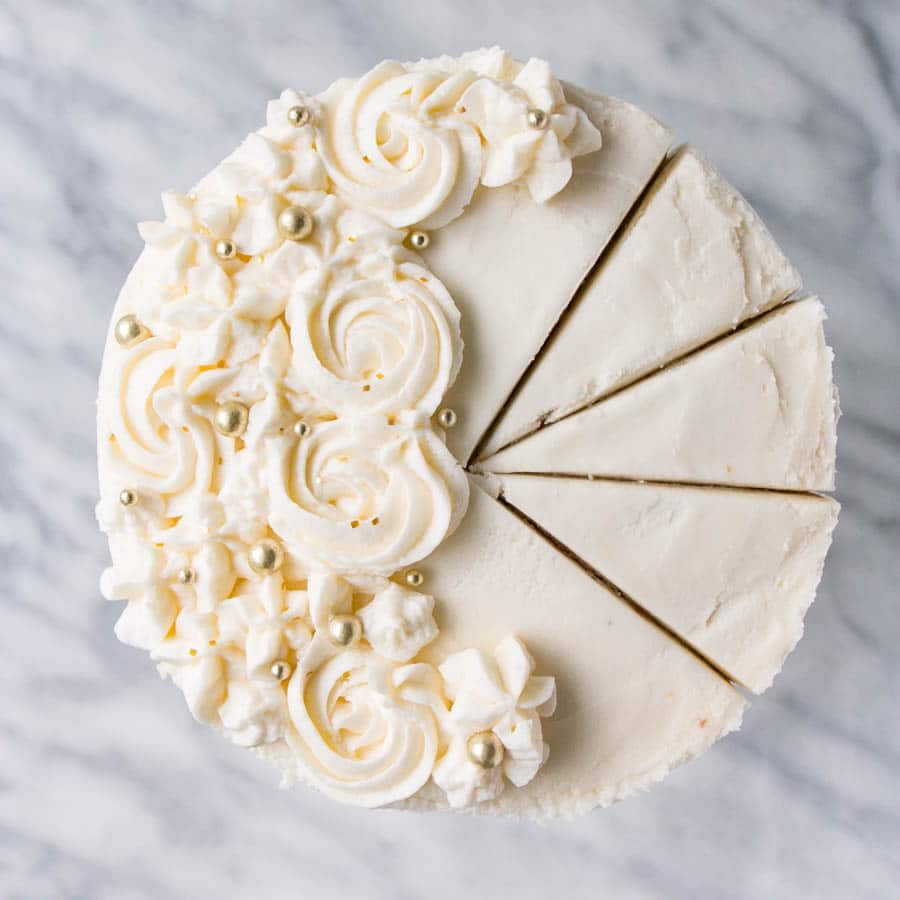 Up close, top down photo of a creamy, rose piped, Vanilla Bean Champagne Cake