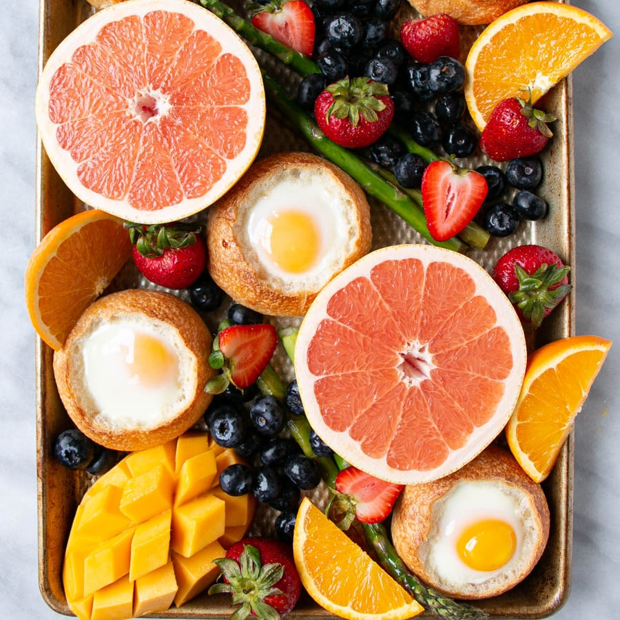 Oven Baked Eggs in buns on a baking tray with bright vibrant fruit and bright green asparagus.