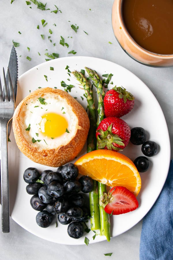 Oven Baked Eggs in Buns with bright berries, oranges, and asparagus.