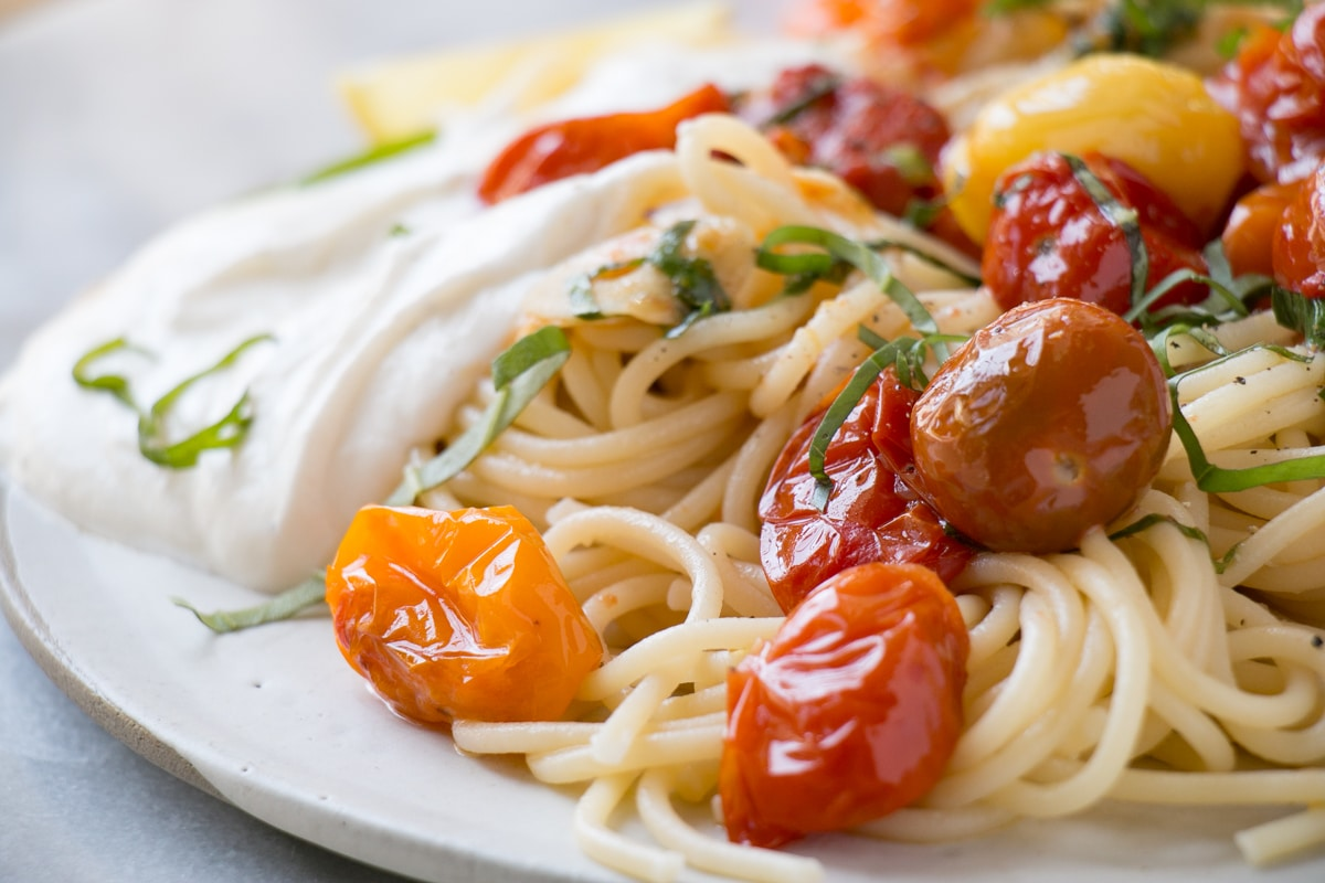 Summer Tomato Pasta with bright red cherry tomatoes, long spaghetti pasta, and a dollop of creamy smooth ricotta
