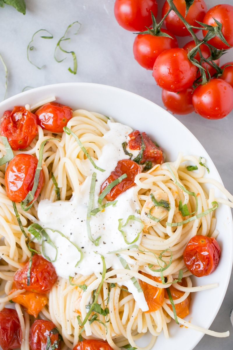 Summer Tomato Basil Pasta with thin long noodles, burst cherry tomatoes, and a big dollop of creamy whipped ricotta cheese.