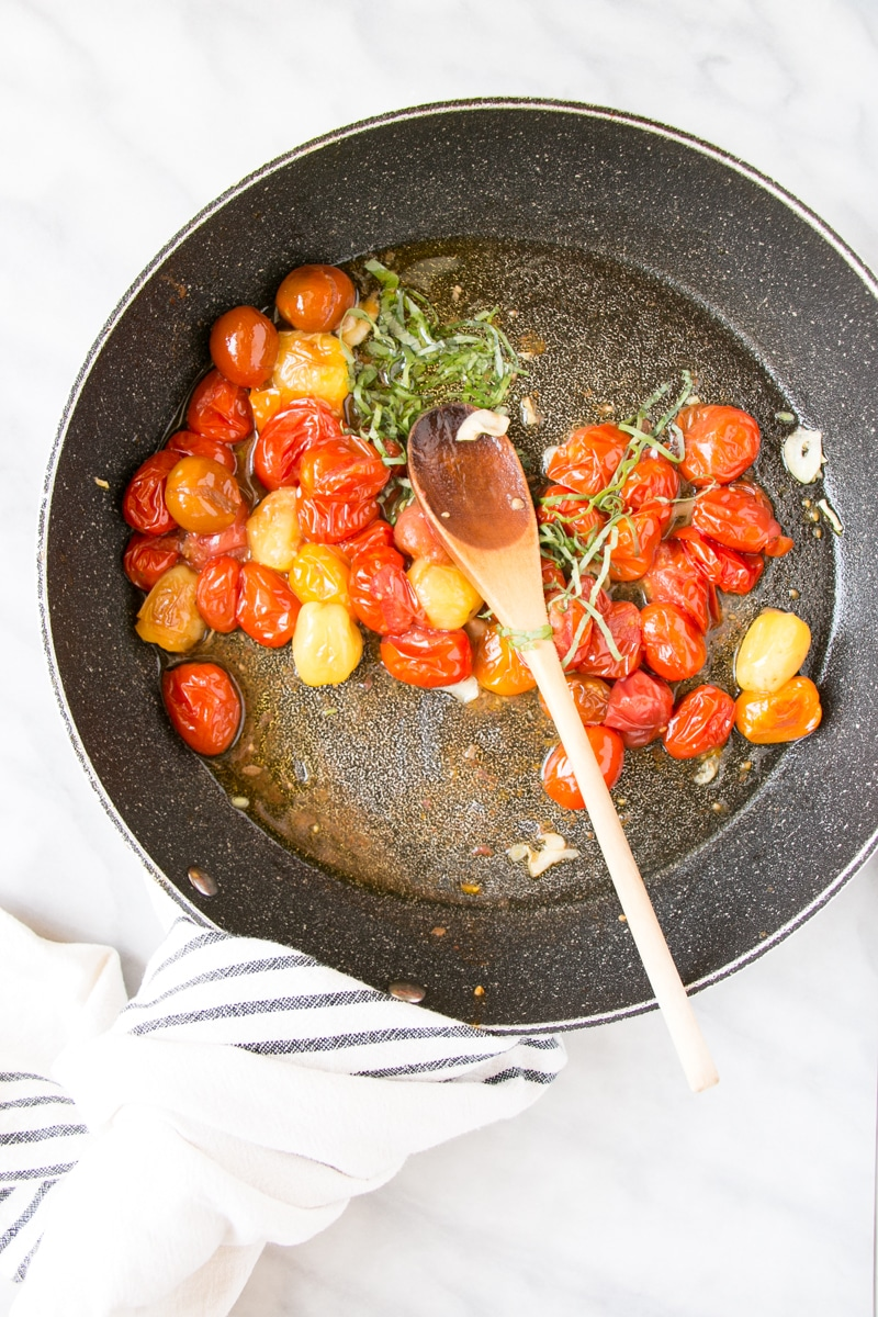 Cooking for Summer Tomato Basil Pasta with the cherry tomatoes bursting in a pan and shredded basil leaves.
