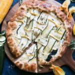 Zucchini Galette on a round wooden board with a blue linen.