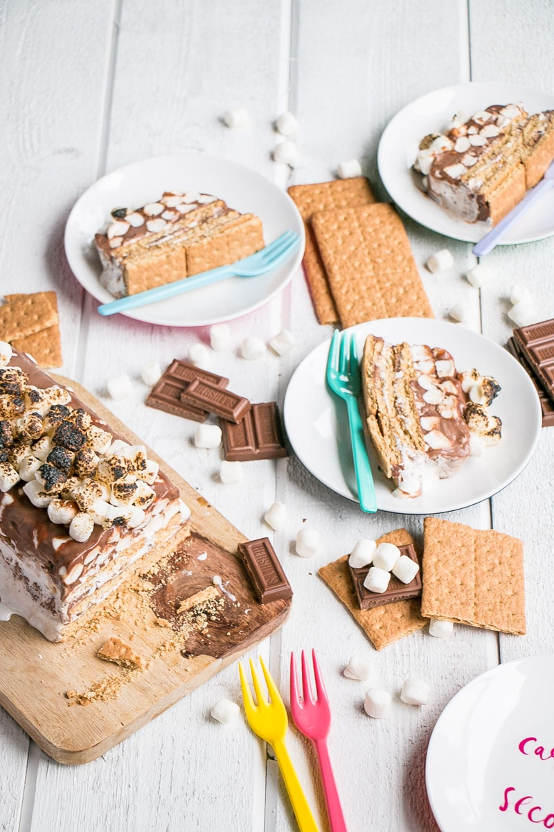 S'mores Icebox Cake cut into slices with graham crackers, chocolate and mini marshmallows around it.