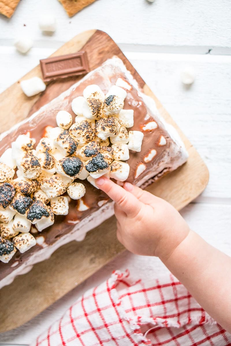 S'mores Icebox Cake with a baby's hand grabbing for the toasted marshmallows on top.