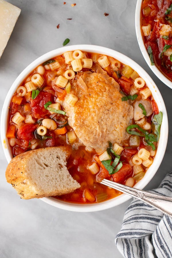 Roasted Chicken Minestrone Soup with herbs in a white bowl topped with fresh fragrant basil and alongside fresh focaccia bread.