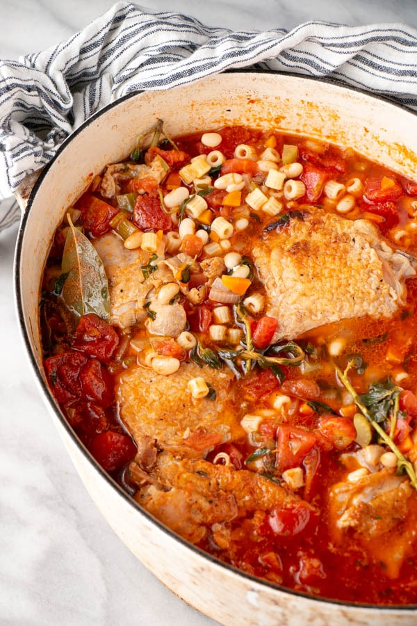 Roasted Chicken Minestrone Soup with herbs in a white Dutch Oven.