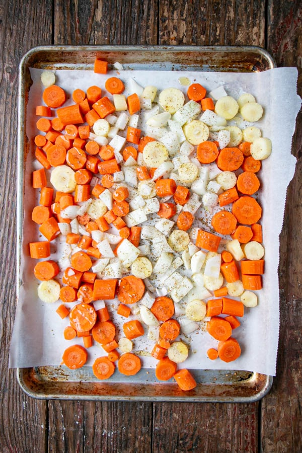 Chopped carrots, onions and garlic on a sheet pan ready to be roasted in the oven.