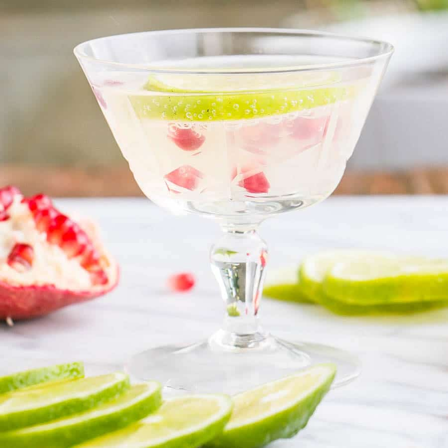 Pomegranate Lime Gimlet in an old fashion glass with bright lime slices and pomegranate seeds.