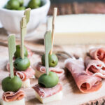 Manchego, Ham & Olive Bites on a wood serving board.