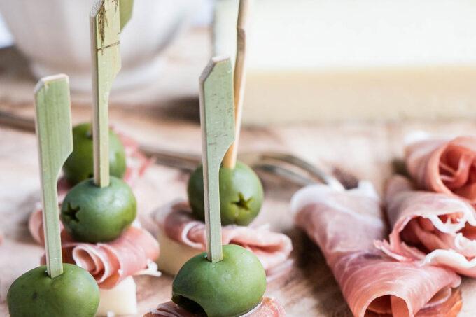 Manchego, Ham & Olive Bites on a wood serving board.