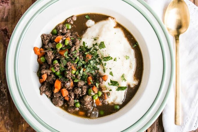 Scottish Mince and Tatties in a shallow bowl with loads of gravy and garnished with chopped parsley.