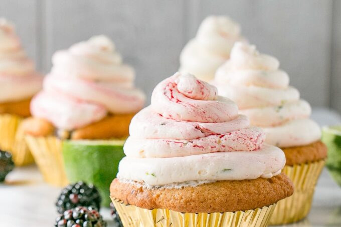 Blackberry Lime Cupcakes with a gold liner and pillowy white and purple streaked swiss meringue buttercream.