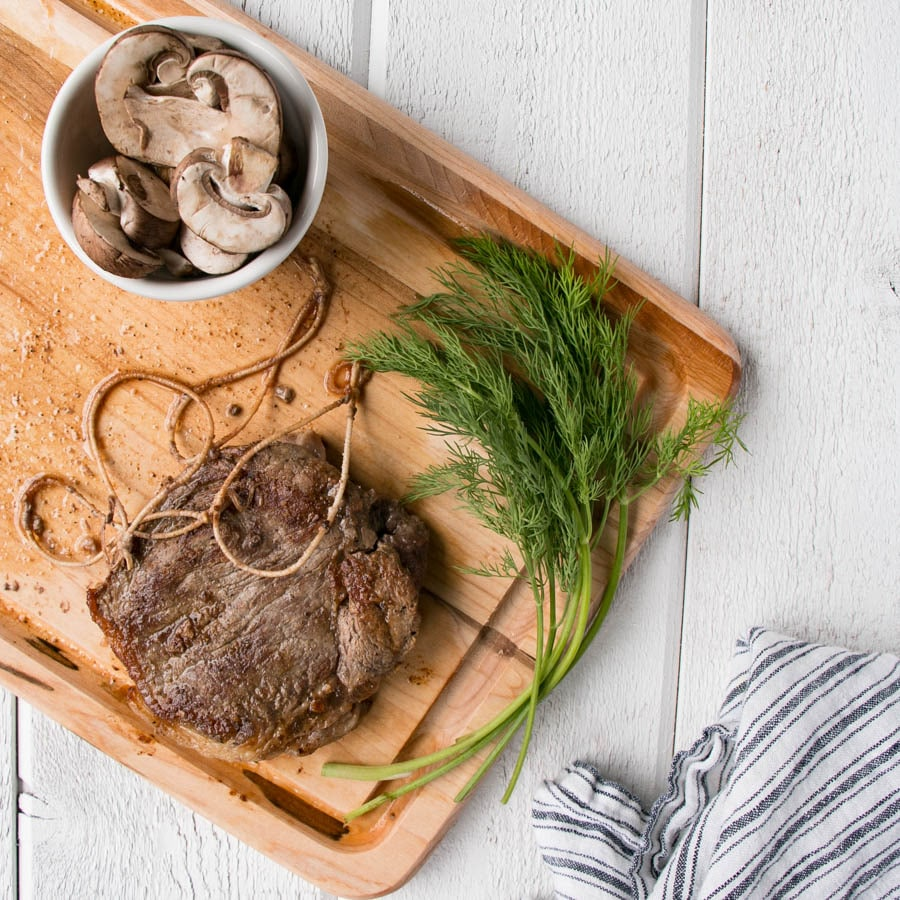 Photo of mushrooms, dill stems, and striploin steak