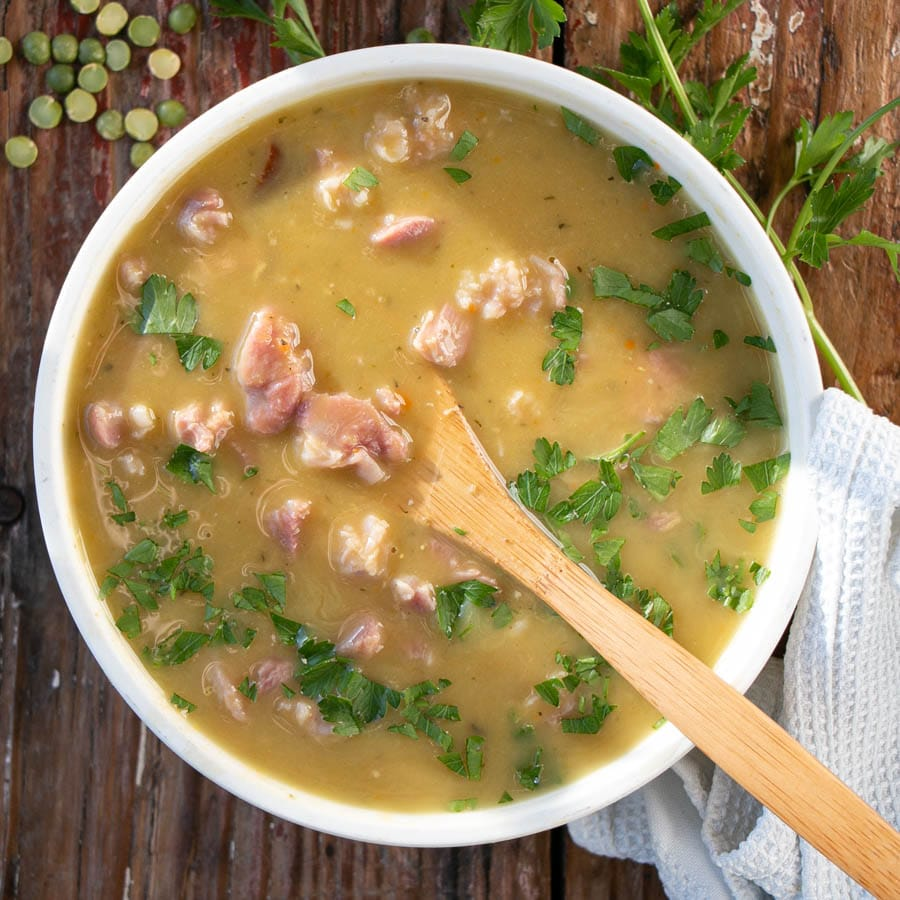 Split Pea and Ham Soup with chunking piece of ham and a sprinkling of parsley on top.