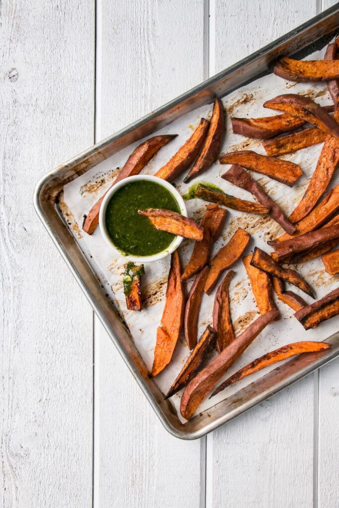 Roasted Sweet Potatoes with Chimichurri is a vibrant and delicious side dish! Super healthy with baked sweet potato fries and herb packed chimichurri sauce. #healthy #sweetpotatoes #fries #chimichurri
