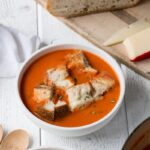 Creamy Tomato Soup with Rosemary Fontina Grilled Cheese Croutons for a cozy soup and grilled cheese experience. #comfortfood #soup #grilledcheese