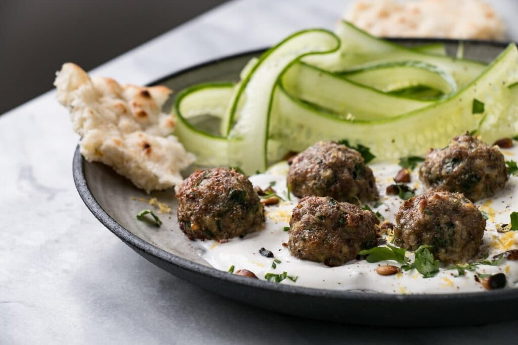 Mini Herby Lamb Meatballs are a quick and easy way to bake juicy and tasty meatballs for dinner! Serve with yogurt and cucumber salad for a refreshing supper! #meatballs #lambs #dinner #weekdaydinner