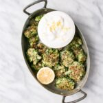 broccoli fritters in a serving dish with lemon yogurt and half of a lemon