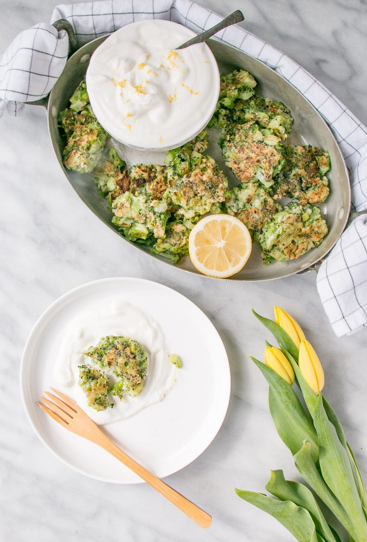 broccoli fritters in serving dish, one on a plate with yogurt dip and yellow flowers