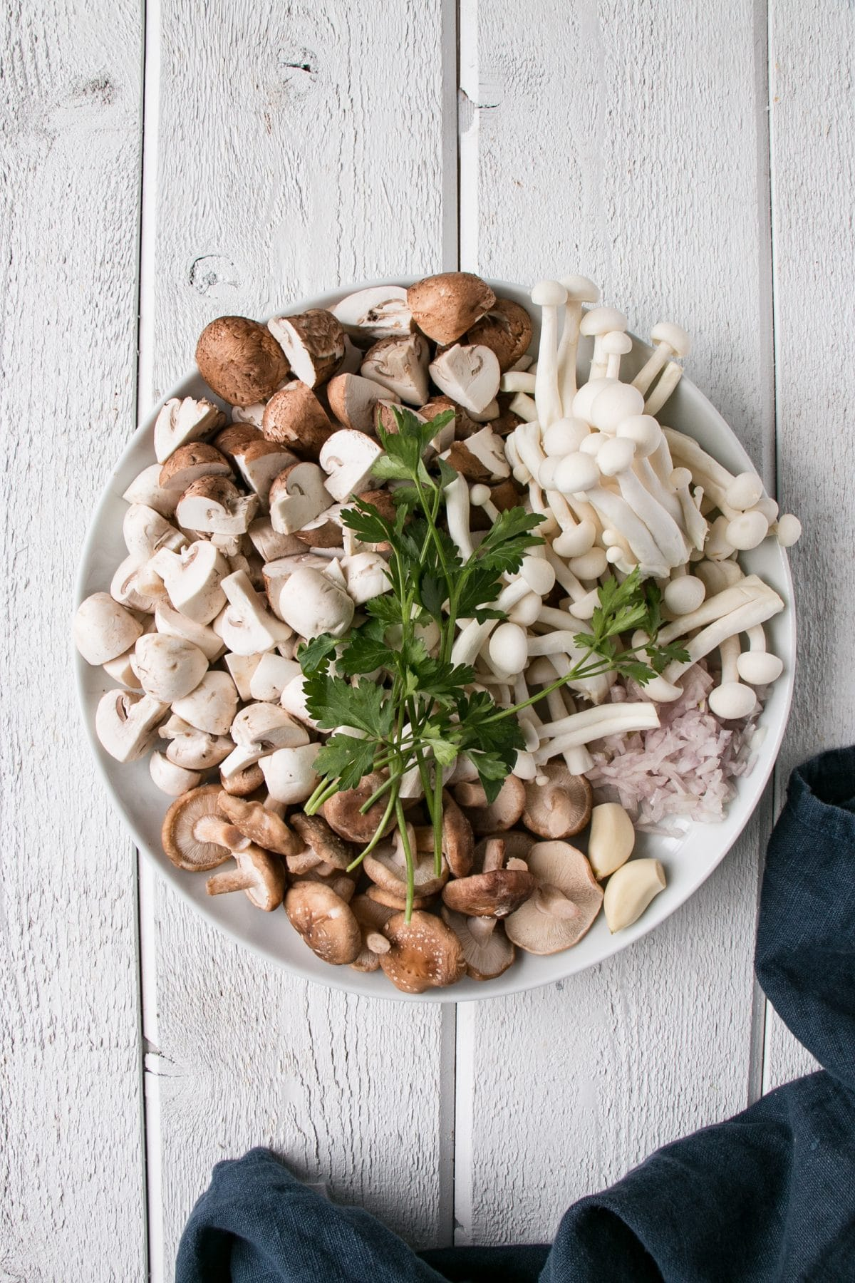 bowl packed with various types of mushrooms, shallots, garlic, and parsley