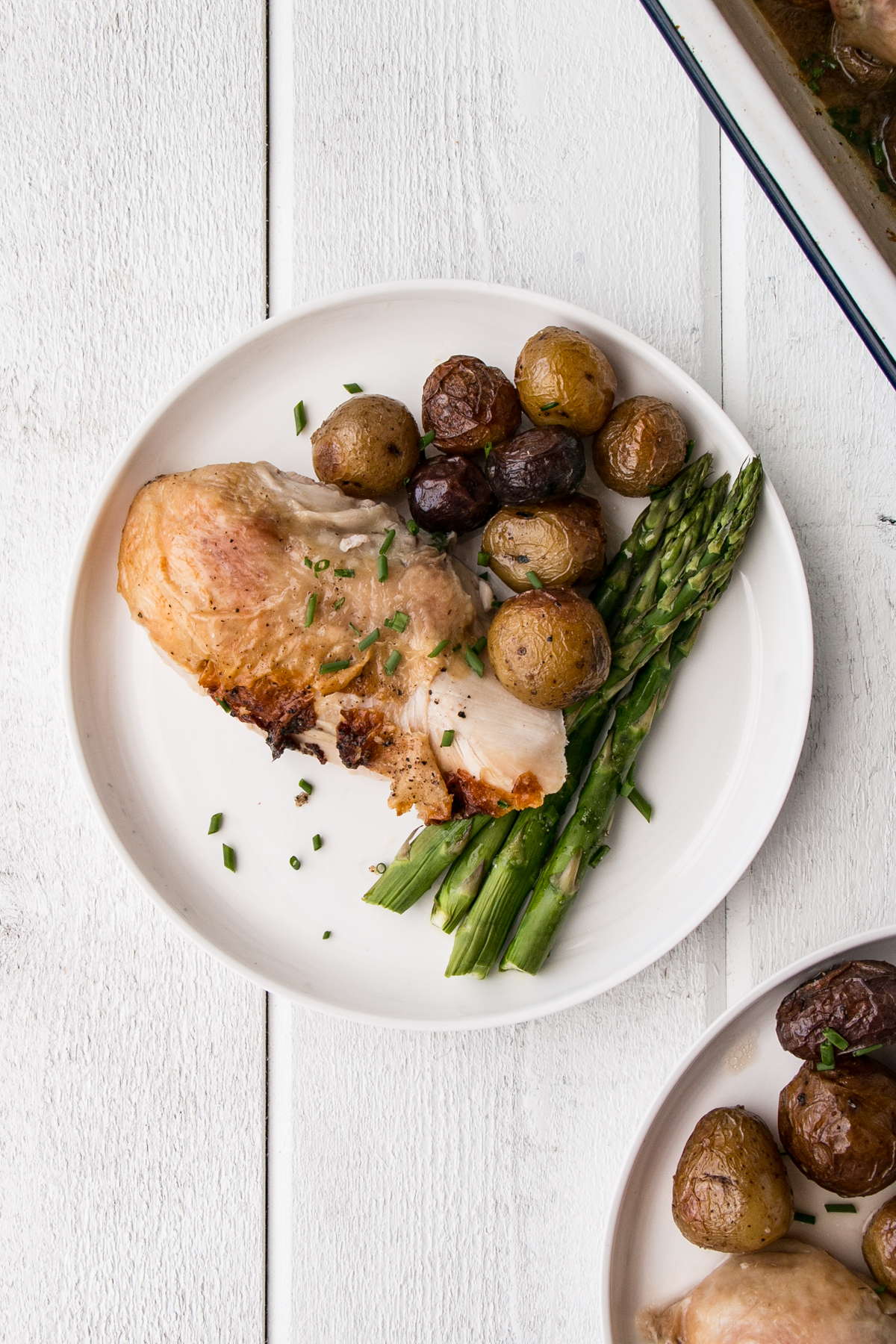 a piece of chicken breast with potatoes and asparagus on a white plate.