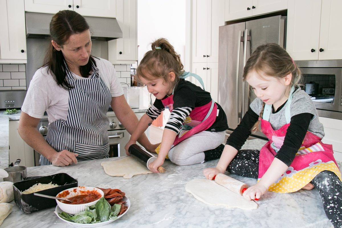 two kids and an adult rolling out dough