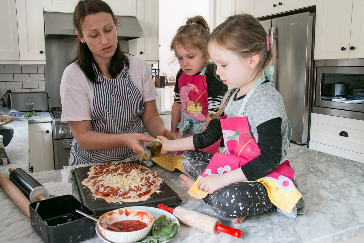 two kids and an adult making pizza