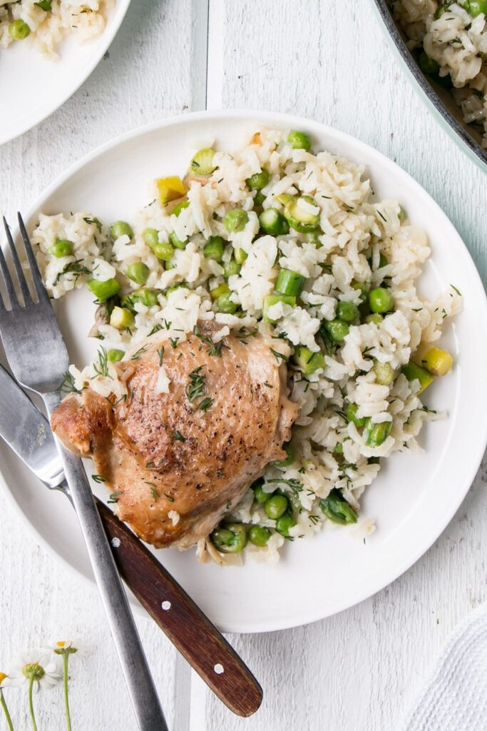 One Pot Chicken and Rice with Peas and Dill in a large pot served on a white plate