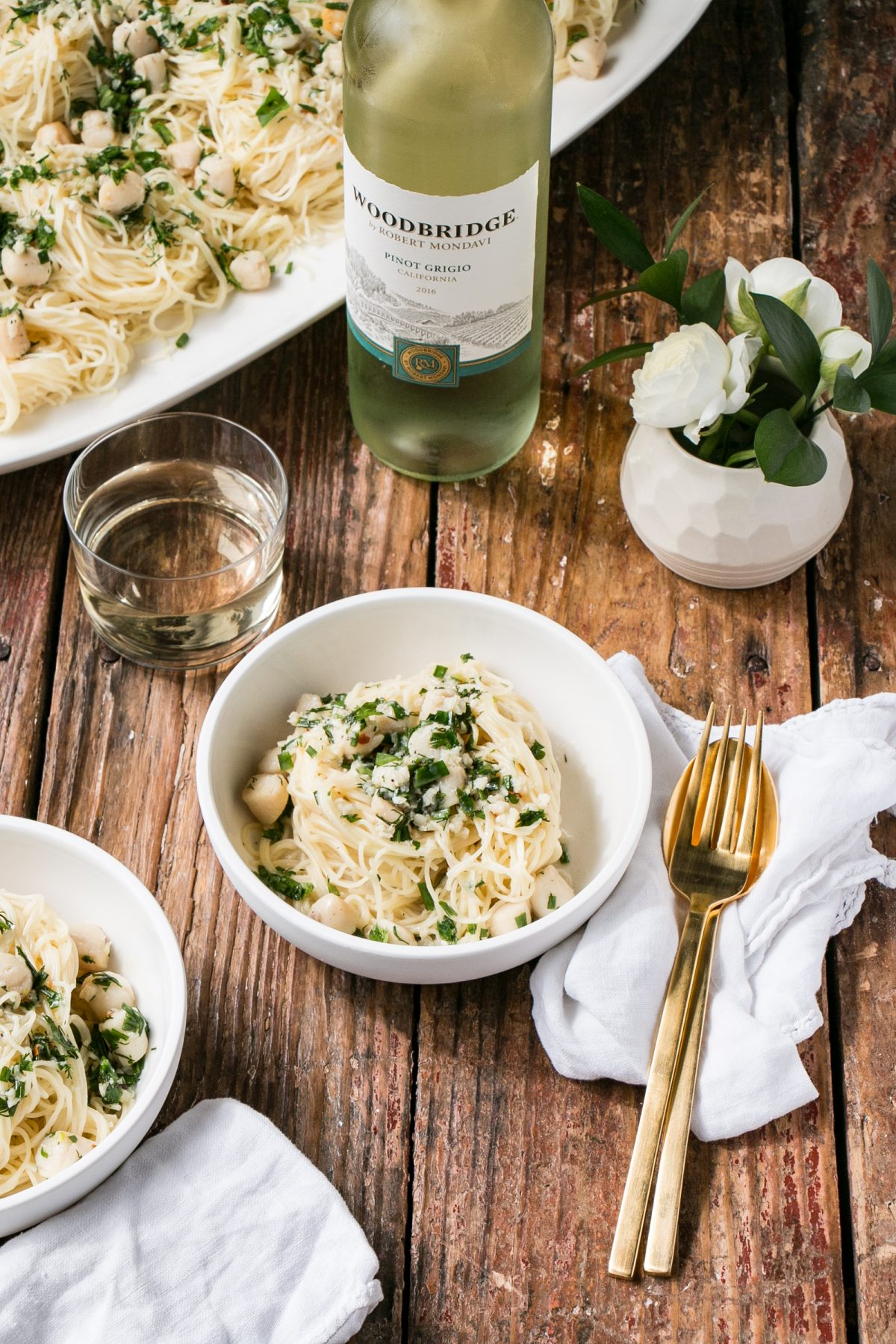 White Wine Butter Scallops over pasta in bowls with a wood background