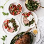 Curry spiced leg of lamb, spinach lentils, tomato salas and lemon yogurt on plates
