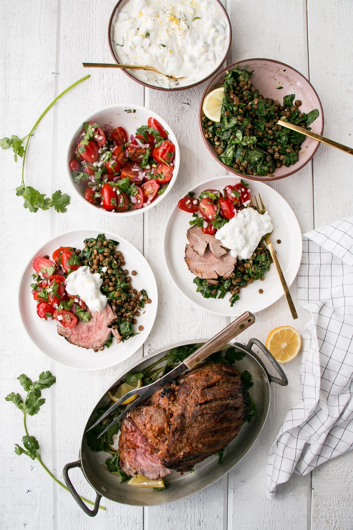 Curry spiced leg of lamb, spinach lentils, tomato salas and lemon yogurt on plates