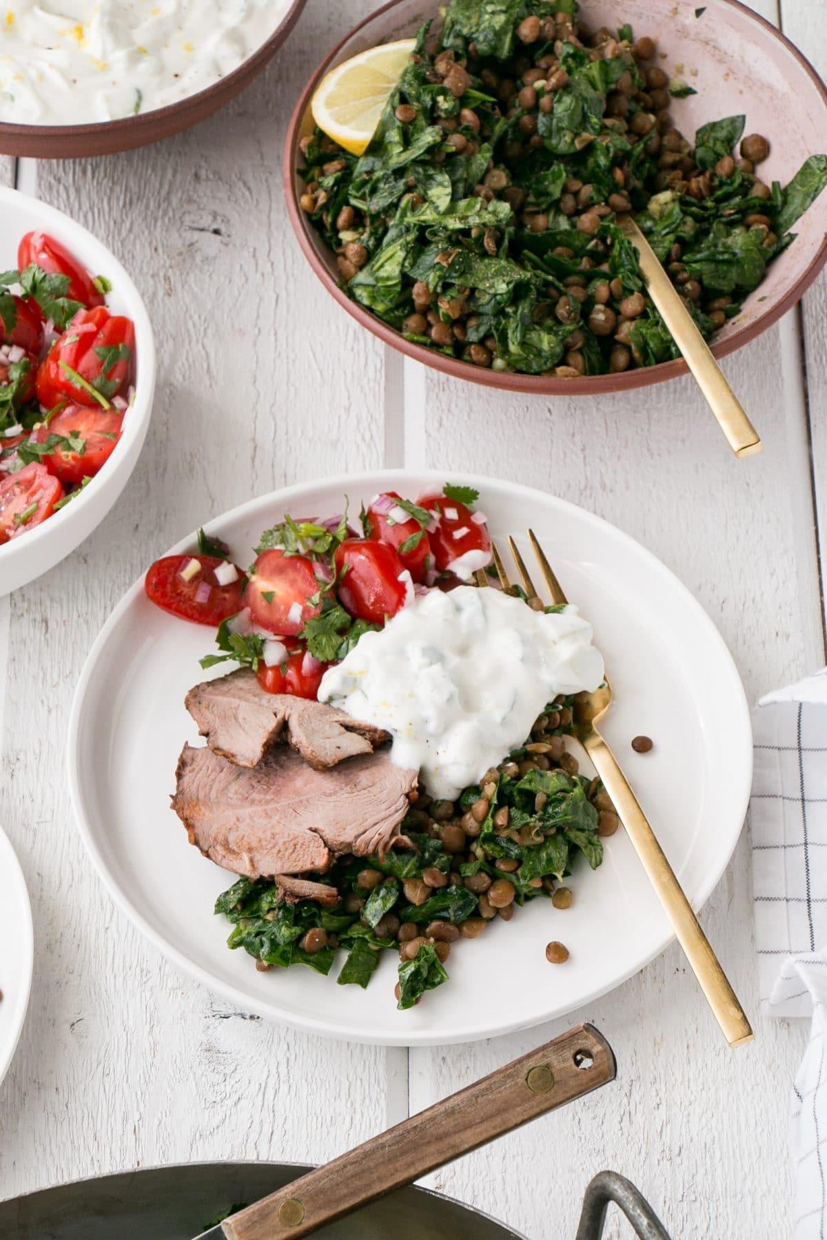 Curry spiced leg of lamb, spinach lentils, tomato salas and lemon yogurt on plate