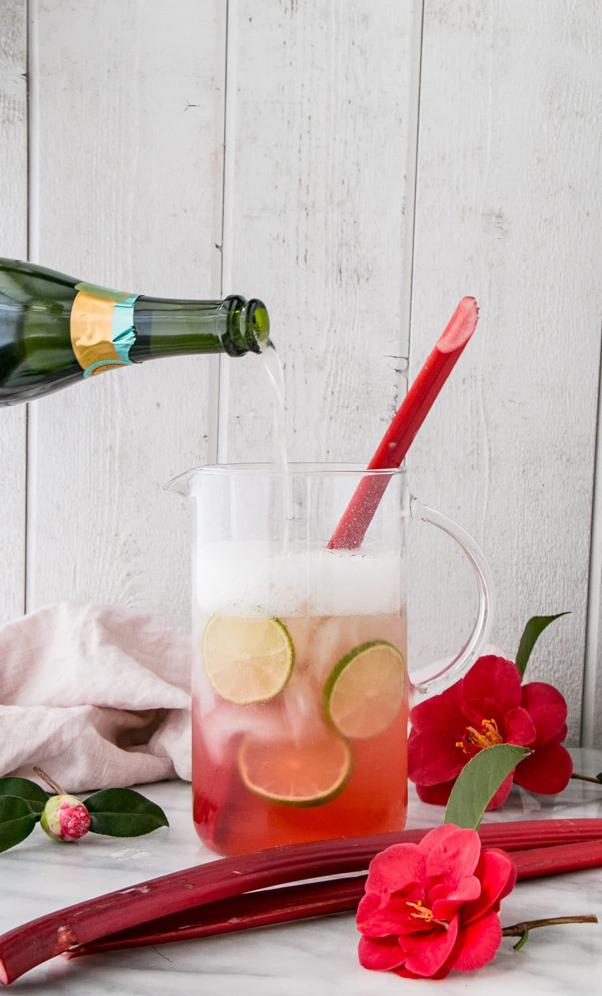 sparkling rhubarb margarita in a pitcher with sparkling wine being added in.